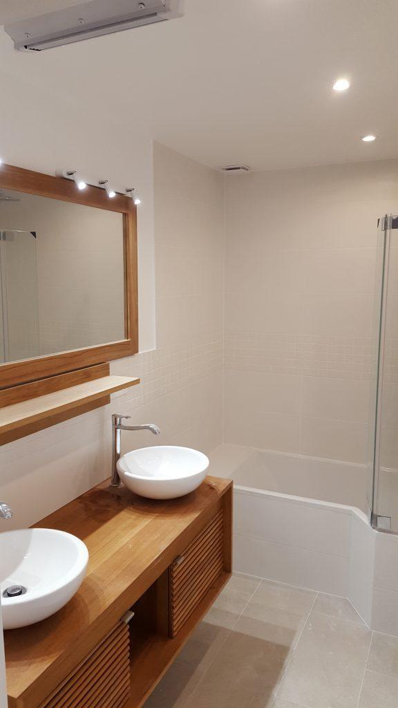 Salle de bains avec double vasque sur meuble en bois